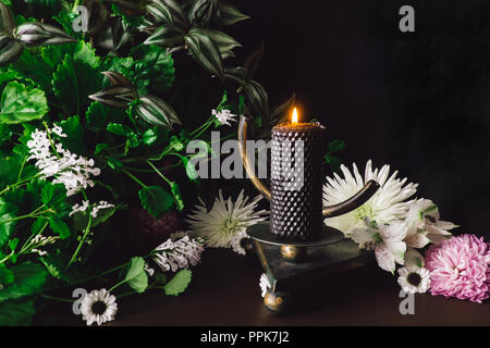 Black Candle on Om Altar with Mixed Flowers and Foliage - Stock Photo