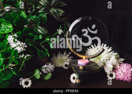 Pink Candle on Om Altar with Mixed Flowers and Foliage - Stock Photo