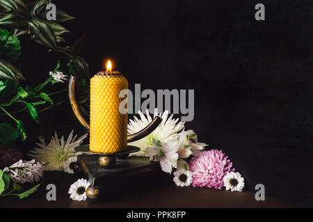 Yellow Candle on Om Altar with Mixed Flowers and Foliage; Includes Space for Copy - Stock Photo