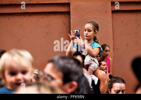 Young girls sitting on her father's shoulders using a smart phone. - Stock Photo
