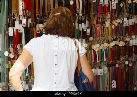A  woman buying a leather belt in a market stall, Siena market, Tuscany Italy Europe - Stock Photo