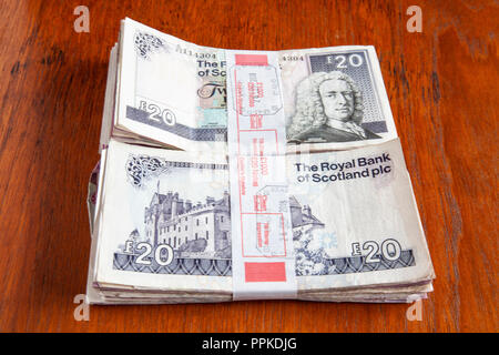 Money left on the table. Two bundles of £1000 each in used Scottish £20 banknotes from the Royal Bank of Scotland and the Clydesdale bank. - Stock Photo