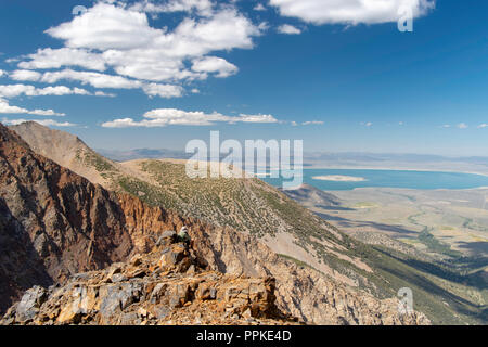Young man contemplating the view of Parker Pass looking eastward from the side of Parker Peak, with a view of Mono Lake in the distance; Ansel Adams W - Stock Photo