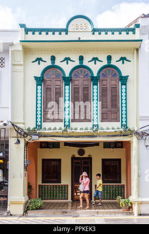 Phuket, Thailand - 2nd September 2018: Tourists walking past a renovated shophouse in Thalang Road. The architectural style is Sino Portuguese. - Stock Photo