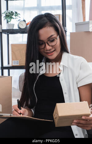asian woman check shipping packages - Stock Photo