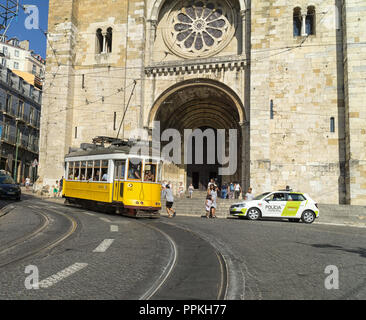 LISBON, PORTUGAL - August 31, 2018: yellow tram line 28 in front of the Se Cathedral; An unidentified boy jumps on a tram. - Stock Photo