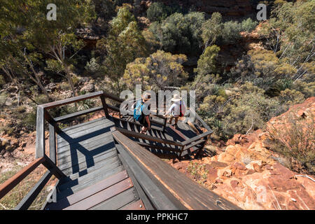 2 tourist wearing huts, walking down wooden stair down in  Kings Canyon, Watarrka National Park , Northern Territory, Australia - Stock Photo