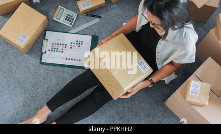 Portrait young woman with check shipping packages - Stock Photo