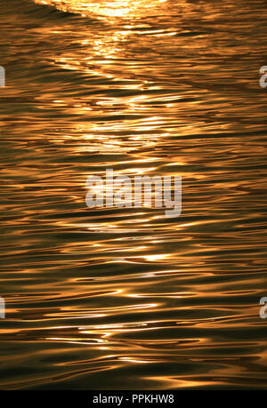 Gorgeous gold color sea water surface with the gentle waves glittering by morning sunlight - Stock Photo