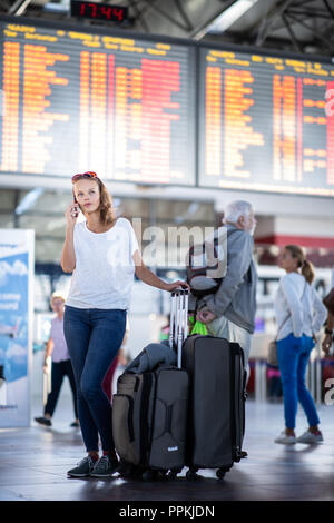 Young woman with her luggage at an international airport, before going through the check-in and the security check before her flight - Stock Photo