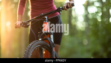 Pretty, young woman biking on a mountain bike enjoying healthy active lifestyle outdoors in summer (shallow DOF) - Stock Photo