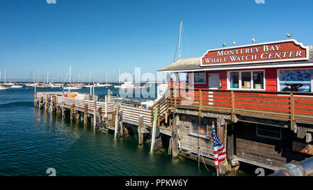 Monterey, CA, USA, 15 September  2018. Monterey  harbor in on a sunny day with cloudless sky  featuring the Whale Watch Center and some boats parked i - Stock Photo