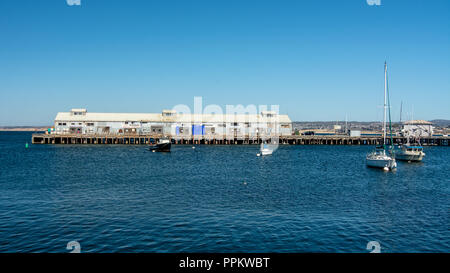 Monterey, CA, USA, 15 September  2018.  Monterey pier 1, a commercial pier, viewed from from pier 2 , mainly touristic, on a blue  cloudless sky day i - Stock Photo