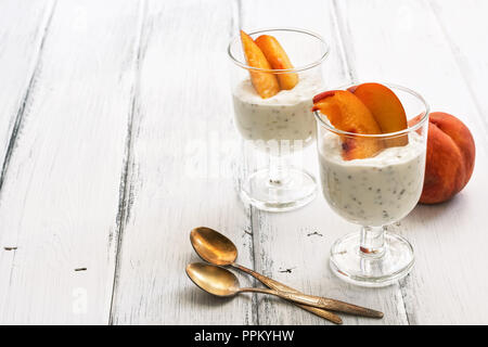A useful breakfast, yoghurt with pieces of peach and chia seeds on a white wooden rustic table. Selective focus, copy space - Stock Photo