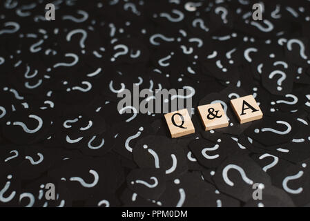 wooden alphabet tiles with Q&A letter on black paper with QUESTION MARK. Concept of Question and Answer Q&A online assist - Stock Photo