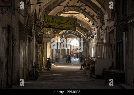 ISFAHAN, IRAN - AUGUST 7, 2018: Street of the Isfahan bazar in the afternoon, in a covered alley of the market. Symbol of the Persian architecture, it - Stock Photo