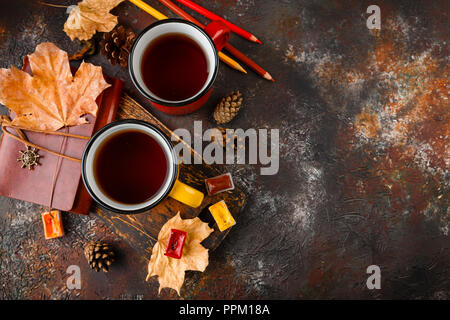 Two colored red and yellow enamel cups of tea, watercolors in cuvettes, colored pencils, autumn maple leaves and bumps on a rusty brown background - Stock Photo