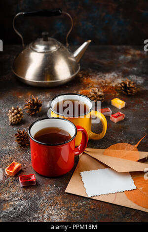 Two colored enamel cups of tea, two envelops, watercolors in cuvettes, , autumn leaves and bumps on a rusty brown background - Stock Photo
