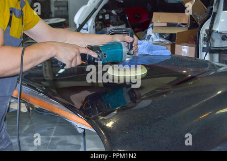 The master man of the detailing in work clothes and dirty hands polishes the bodywork of the bonnet of the car in black with a polishing machine in th - Stock Photo