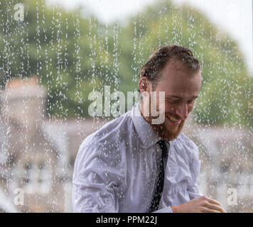 A man in a suit caught in a very heavy rain shower - Stock Photo