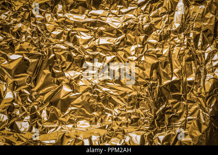 The close up of a coppery surface of aluminum foil. Metallic background. - Stock Photo