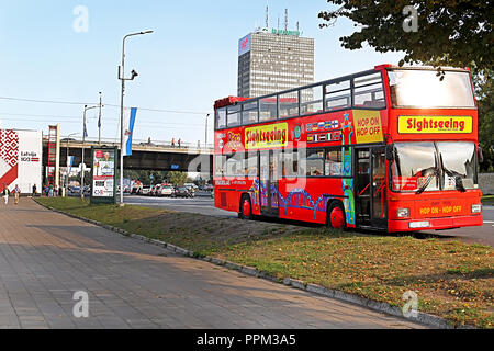 RIGA, LATVIA - AUGUST 29, 2018: Touristic red double-decker hop-on hop-off City Sightseeing tour bus on the street of Riga city near embankment - Stock Photo