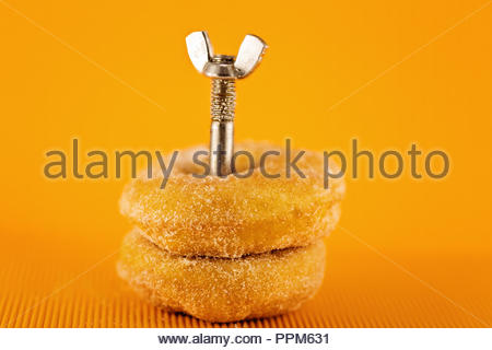 A conceptual image for weighing up whether to eat a doughnut or go to the gymnasium - Stock Photo