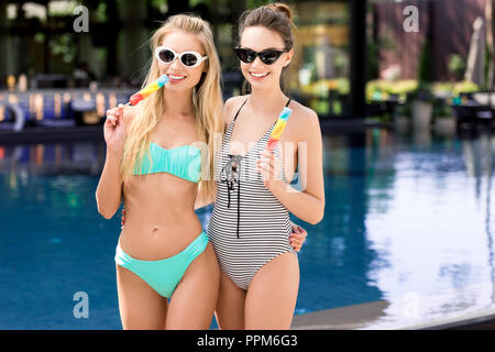 happy young embracing women in swimsuit and bikini with popsicles looking at camera at poolside - Stock Photo