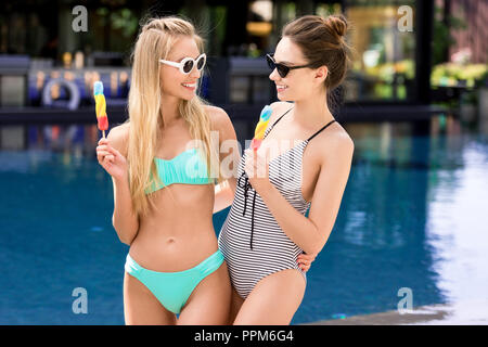 happy young embracing women in swimsuit and bikini with popsicles at poolside - Stock Photo