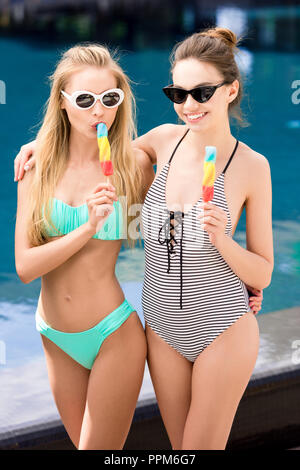 beautiful young embracing women in swimsuit and bikini eating popsicles at poolside - Stock Photo