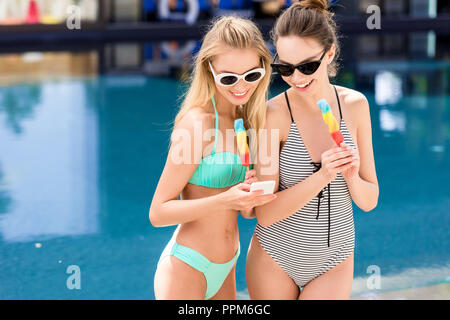beautiful young women in swimsuit and bikini with popsicles at poolside - Stock Photo