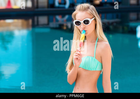 beautiful young woman in bikini and vintage sunglasses eating colorful popsicle at poolside - Stock Photo