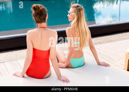 rear view of young women relaxing on sun lounger at poolside - Stock Photo
