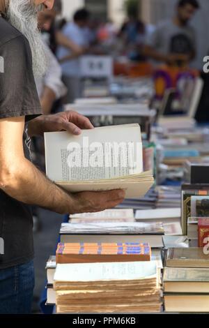 LISBON, PORTUGAL, September 01, 2018: Rua Anchieta weekend book market Chiado district; Unidentified man with a gray beard is watching a book. - Stock Photo