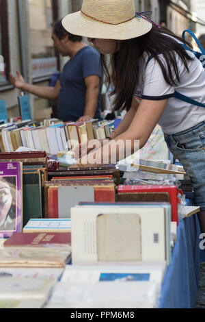 LISBON, PORTUGAL, September 01, 2018: Rua Anchieta weekend book market Chiado district; Unidentified woman in straw hat is watching a book. - Stock Photo