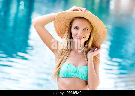 beautiful young woman in straw hat and bikini looking at camera at poolside - Stock Photo