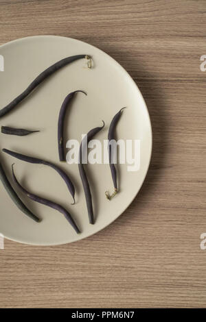 Purple Green Beans Scattered on a Plate Vertical Overhead View - Stock Photo