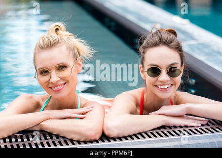close-up portrait of attractive young women relaxing in swimming pool and looking at camera - Stock Photo