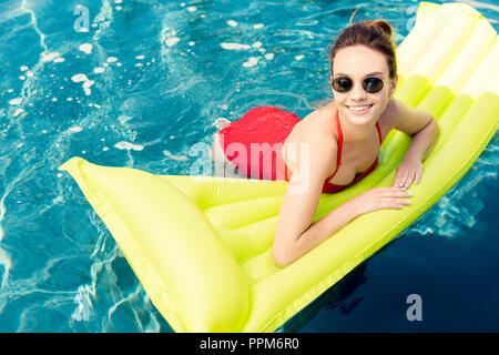 attractive young woman lying on inflatable mattress in swimming pool - Stock Photo