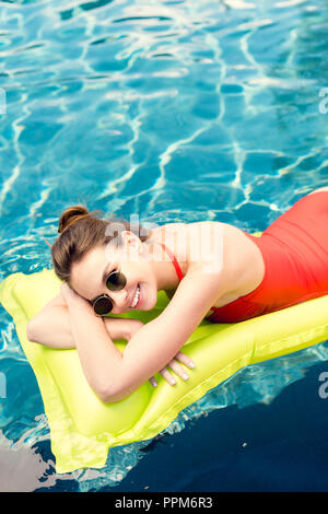 happy young woman lying on inflatable mattress in swimming pool - Stock Photo