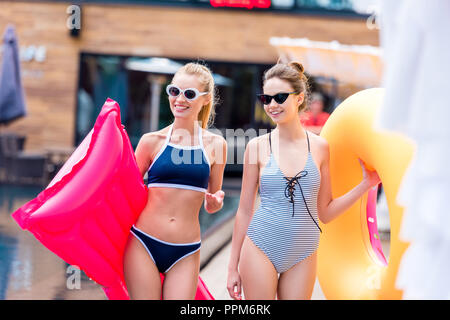smiling young women with inflatable mattress and ring at poolside - Stock Photo