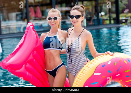 happy young women with inflatable mattress and ring at poolside - Stock Photo