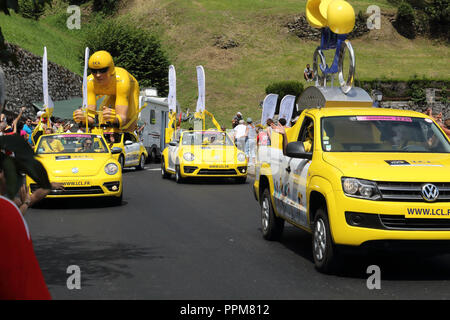 The yellow Le Crédit Lyonnais cars throwing free gifts during the 2018 Tour de France 17th stage in Soulan, French Pyrennìees, ans supporters. - Stock Photo