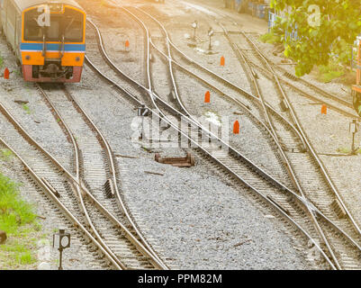 Train track and traffic sign between railway. Journey by train in the morning with warm sunrise light. Local transportation. Travel on summer by train - Stock Photo