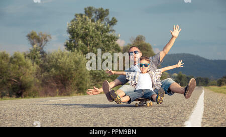Father and son playing on the road at the day time. People having fun outdoors. Concept of friendly family. - Stock Photo