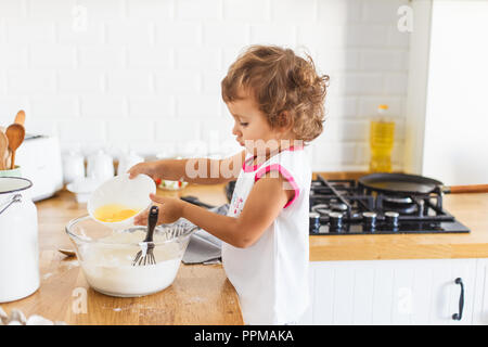 Little girl preparing dough for pancakes at the kitchen. Concept of food preparation, white kitchen on background. Casual lifestyle photo series in re - Stock Photo