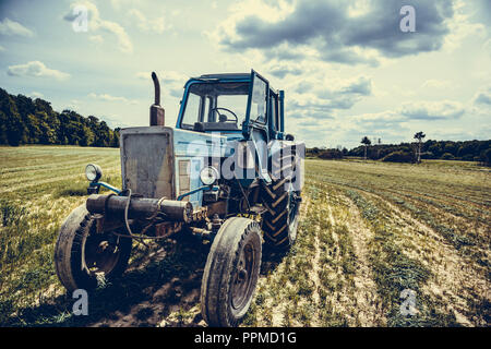 Old tractor in the field, beautiful view - Stock Photo