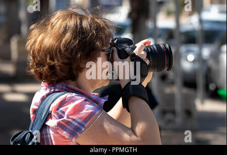 Women taking pictures with digital camera (DSLR) in Haifa, Israel - Stock Photo