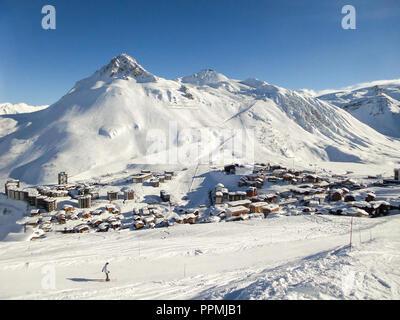 Ski resort of Tignes in winter, ski slope and village of Tignes le lac in the background - Stock Photo