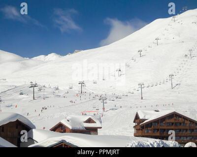 Ski resort of Tignes in winter, ski lifts and village of Tignes le lac in the foreground - Stock Photo